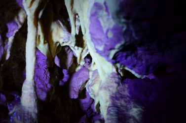 UV light highlighting rock formations in Kelly Hill Caves.